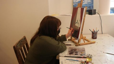 """Junior Brenna Batchelder works on her oil painting with the studio coordinator Sophie Newell. """"I love seeing mentees come into their own through art,"""" Newell said. """"Sometimes there"""