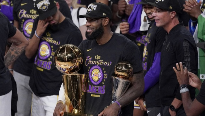 "Laker forward LeBron James holds his fourth Larry O'Brien trophy and Finals MVP award. James is the only player in the four major American sports (Football, Baseball, Basketball, Hockey) to win a playoff MVP award with three different teams. ""I've got a lot of years left in the tank,"" said James, who is 35 years old and in his eighteenth season. ""I'm still at the top of my game."""