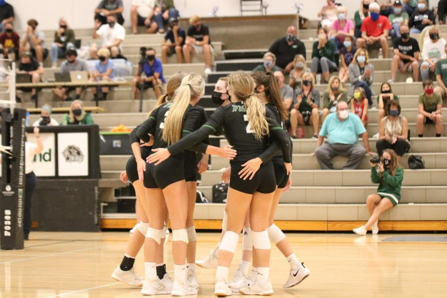 "Millard West volleyball members celebrating during a match against Millard South. The Wildcats won this match in a sweep over the Patriots. ""We've had some ups and downs this year but we are all very close and have a really great culture throughout the team,"" senior Bridget Smith said. ""We always find a way to push through a tough match and we learn from each game."""