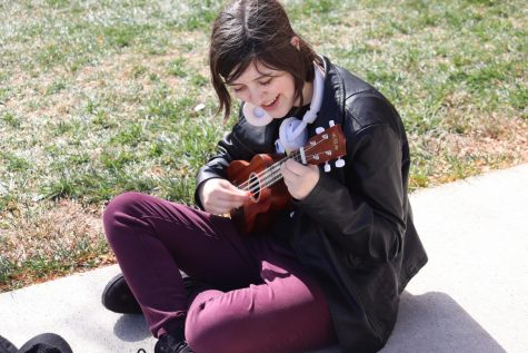 "Sitting on the cement outside, junior Chloe Brandenburg strums a song on the ukulele as they sing along with the music. Brandenburg has recently taken up the hobby of playing the ukulele again and shares their music during lunch. ""It makes me feel really happy when people listen to me at lunch,"" Chloe Brandenburg said. ""I am very good at trashing on myself, so it's a welcome change."""