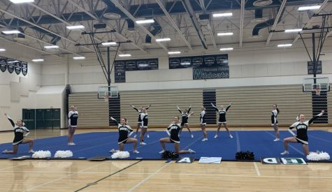 """The varsity team strikes their first pose in their Tumbling, Non-Building routine. For their first competition of the season being completely virtual, the girls look forward to hopefully being able to compete in person. """"I think it makes it a little harder to get a feel for what a comp day is really like, especially for the freshman,"""" senior Delaney Cutler said. """"Luckily on the showcase night, we had a good amount of people in the crowd yelling with us which really helped us out."""""""