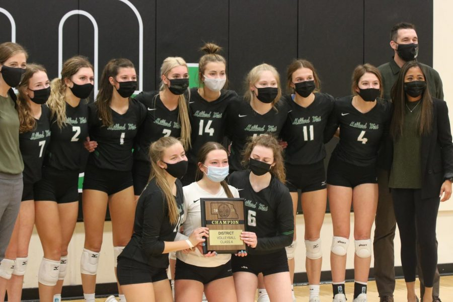 """Millard West takes a picture with their District Championship Plaque after beating Marian three sets to one. """"It felt good and it was an accomplishment to make it to State all four years that I was here,"""" senior Bridger Smith said."""
