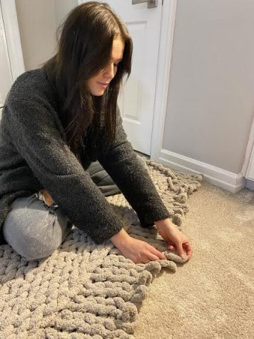 "Senior Paige Stobbe adds to her current creation with another row of chunky yarn. She has been hand-knitting these trendy blankets to sell during the holidays. ""There has been quite a shortage in yarn lately,"" Stobbe said. ""That is one challenge that I have run into, but I hope to keep it going."""