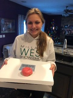 "Junior Campbell Macy stands holding a box of the donuts that she designed. On the top of the box, there is a donut with red hot frosting. ""We turned the cinnamon candy into a very thick syrup and emulsified that into our standard white icing,"" Bob's Donuts chef Keri Tull said. ""We already had an apple cake donut that we were selling so we used that. The toppings are a syrup that we made and crushed cinnamon candy."""