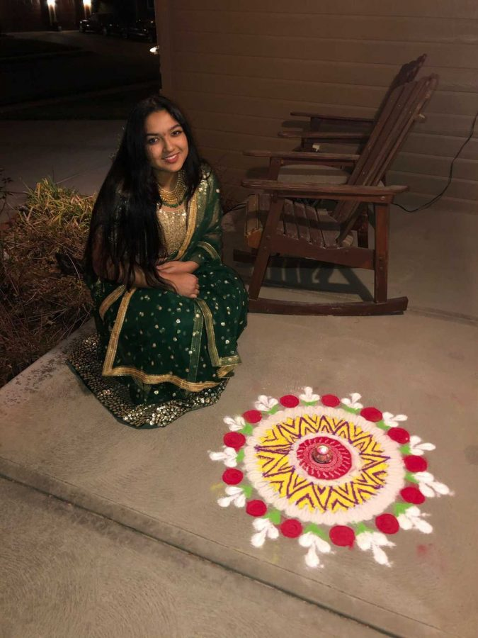 "Shreeya is pictured wearing her new Indian clothes with the rangoli her mom and her made. She celebrated Diwali ""festival of lights"" on November 14th. ""This day celebrates the return on Rama, an incarnation of Lord Vishnu, and his wife Sita, an avatar of Goddess Lakshmi, to Ayodhya,"" senior Shreeya Mishra said. "" After his 14 years in exile, Rama returns after defeating the evil Ravana, which is why this day celebrates good over evil. Because of their return the residents of Ayodhya had a celebration and lit clay lamps."""
