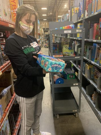 "Senior Delaney Cutler scans a UPC label with her handheld as she picks orders for Fat Brain Toys. Cutler works as seasonal help at the local toy company based in Elkhorn, Nebraska. ""Working here feels really good,"" Cutler said. ""You get done and know you just helped the company to send gifts to families all over the country for their loved ones to open on Christmas."