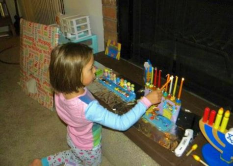 "A young Friedland lights her hanukkiah. ""I was raised Jewish so I have celebrated it [Hanukkah] since I was a baby,"" junior Abby Friedland said. ""Hanukkah, to me, is just family time, like many who celebrate Christmas. It's a good way to feel connected to those around you."""