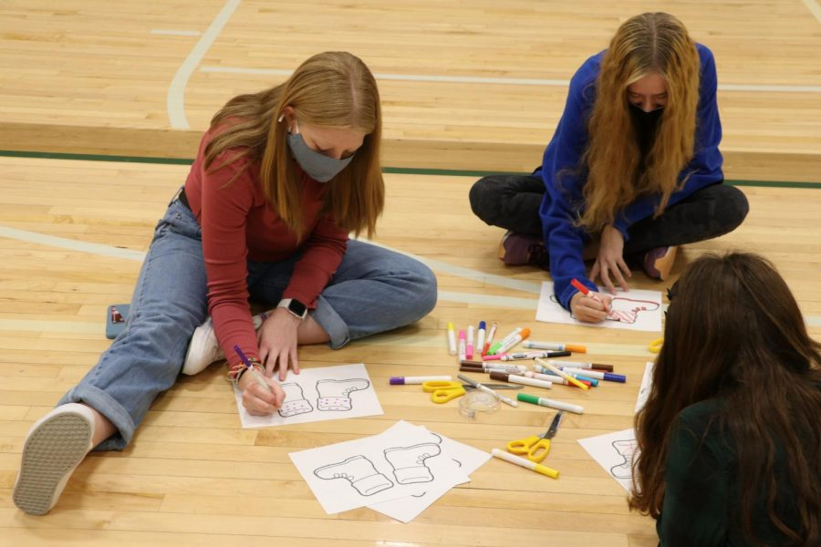 The club members sit in Wildcat 1 cutting out and coloring the shoes for the teachers.