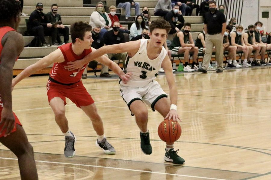 "Senior Dustin Hatch driving past sophomore Brock Murtaugh of Millard South in the opening round of the metro tournament. Hatch had 14 total rebounds and 10 total points throughout the tournament. ""As long as we play to our true potential and continue to improve every practice, I know we can be a playoff team,"" Hatch said. ""My goal going into the season was to play in Lincoln, and I believe we have a shot at performing well in the state tournament. If things go right and we play perfect, winning a championship is a possibility."""