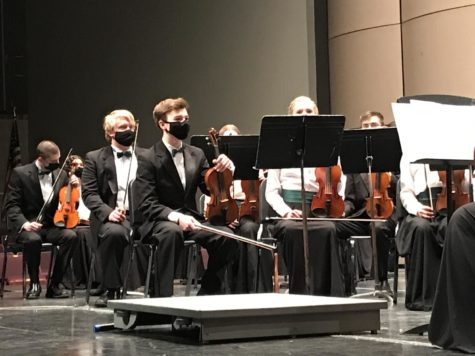 """Members of the symphony orchestra sit waiting to start their next song. """"Students, in general, were pleased to have the opportunity to finally perform for a live audience, and I haven"""