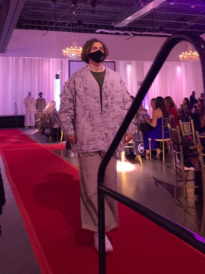 Senior Sam Falter walks down the red runway showing off his camo outfit. Falter has participated in five fashion weeks in the past three years.