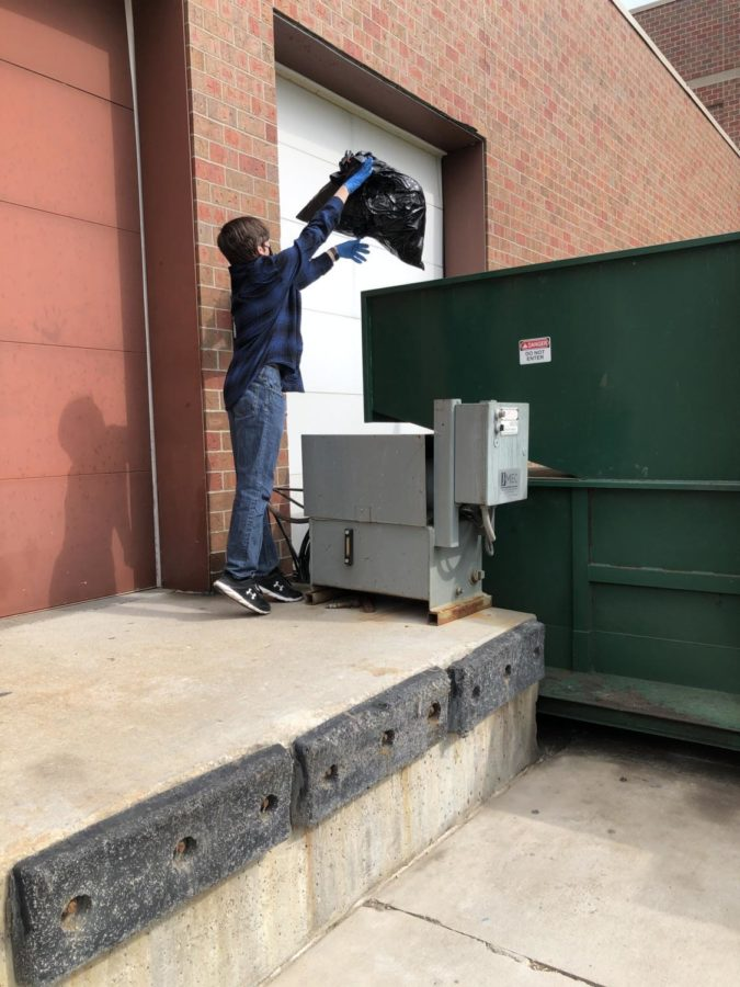 """Junior Michael Boehm tosses his trash bag into the dumpsters after spending time cleaning up the campus. """"I think it is immensely important to celebrate Earth month at West because it gives us time to focus on the planet for at least a month out of the year,"""" Boehm said. """"If we are able to keep the momentum from Earth Month going forward, it can launch into a whole year of celebrating our planet by keeping it clean and habitable. It becomes a domino effect of one upstanding student inspiring another student to save our planet."""""""
