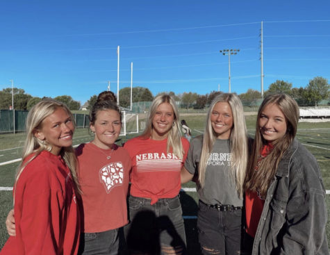 """Seniors Dana Summers, Olivia Petersen, Carli Houfek, Jaya VanAckeren and Megan Forst pose together on the turf field with their college shirts representing where they will attend. """"I will forever be grateful for my time at Millard West,"""" Houfek said. """"I am excited to start a new chapter, but will definitely miss my friends."""""""