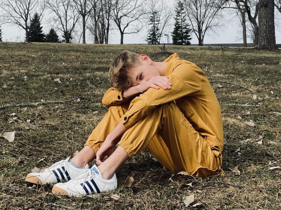 """Junior Connor Thelen poses for a photo in a yellow jumpsuit. Wearing bold outfits to school has become a form of expression for Thelen in the last year. """"Anyone can do it,"""" Thelen said. """"More people are gonna support you than are gonna hate you. It's just that the haters speak louder."""""""