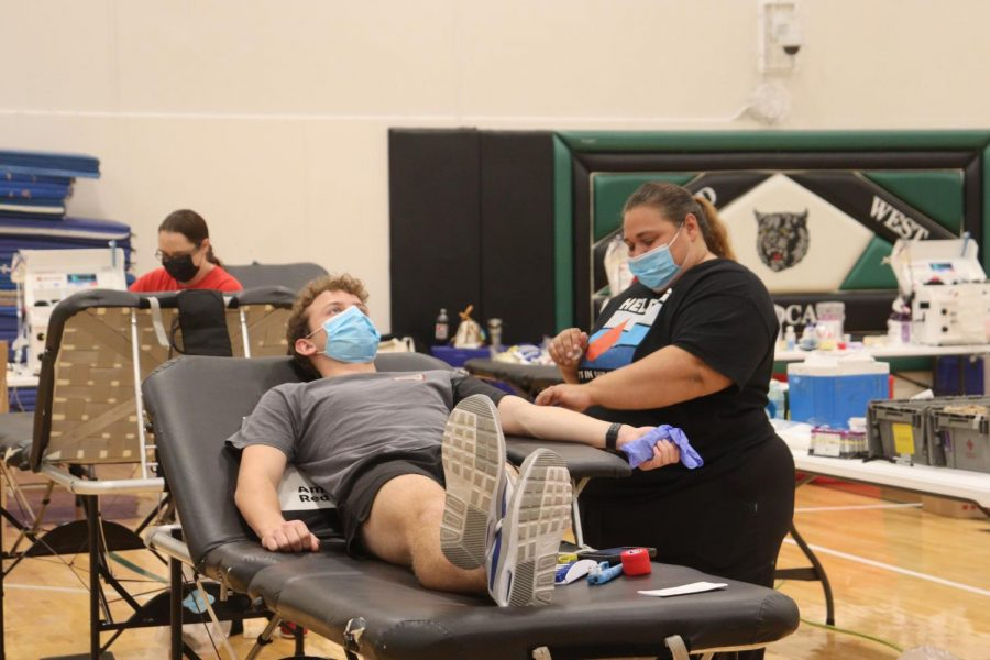 """Donating blood at the Millard West blood drive, sponsored by HOSA, senior Luke Hudek waits for a Red Cross nurse to find a usable vein. Red blood cell and platelet transfusions can not be manufactured and can only come from donations. """"This was my first time donating blood,"""" Hudek said. """"I decided to donate because I knew it was for a good cause. Donating blood is important because it can save lives and it doesn't have any harm on the person donating."""""""