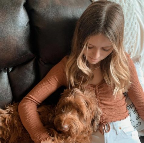 Freshman Lily Dotson cuddles with her dog. She underwent two and a half years of intense treatment. We are so thankful she continues to be a warrior even when people don't see the battle, mother Susie Dotson said. We are proud of all she has overcome.