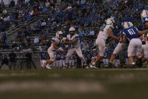 Sophomore Brody Peterson hands the ball of the senior Nathan Pederson against the Lincoln East Spartans. The Spartans won 41-10.